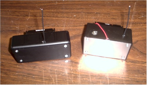 Front view of small plastic boxes containing the wireless intercom with headset jacks and antennas showing.